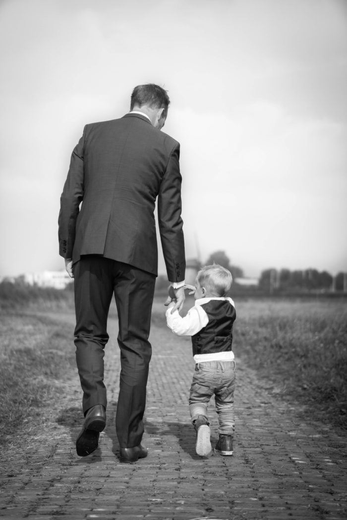 Older man in a business suit walks down a brick path while holding the hand of a young three-year-old boy.