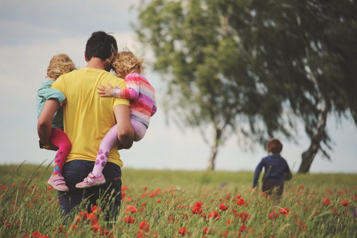 """""""Respectful parenting"""" father carries young children in his arms while another child runs into a field of flowers."""
